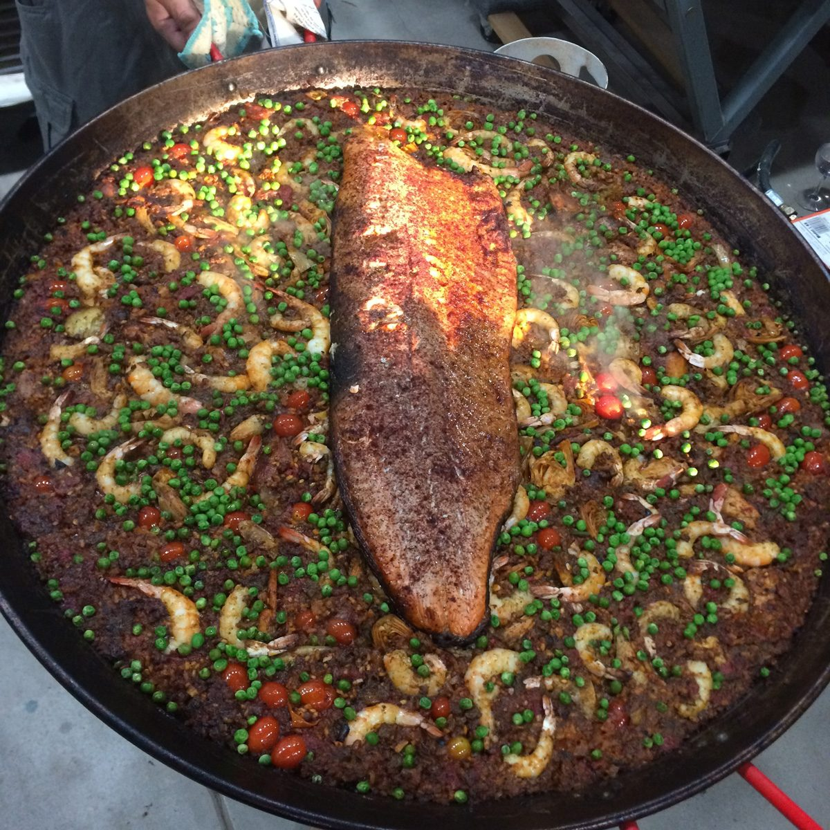 In Santa Fe, the Don of Making Art Safely grills a slab of salmon with chipotle to lay on top of the finished paella.